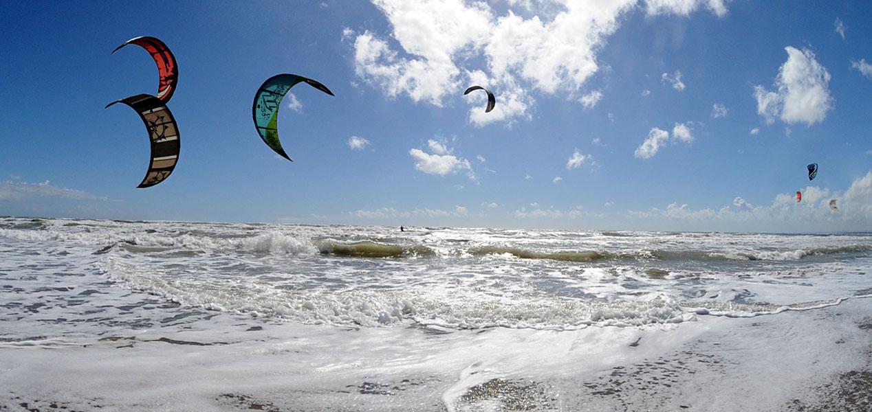 surfisti con aquiloni in un mare mosso